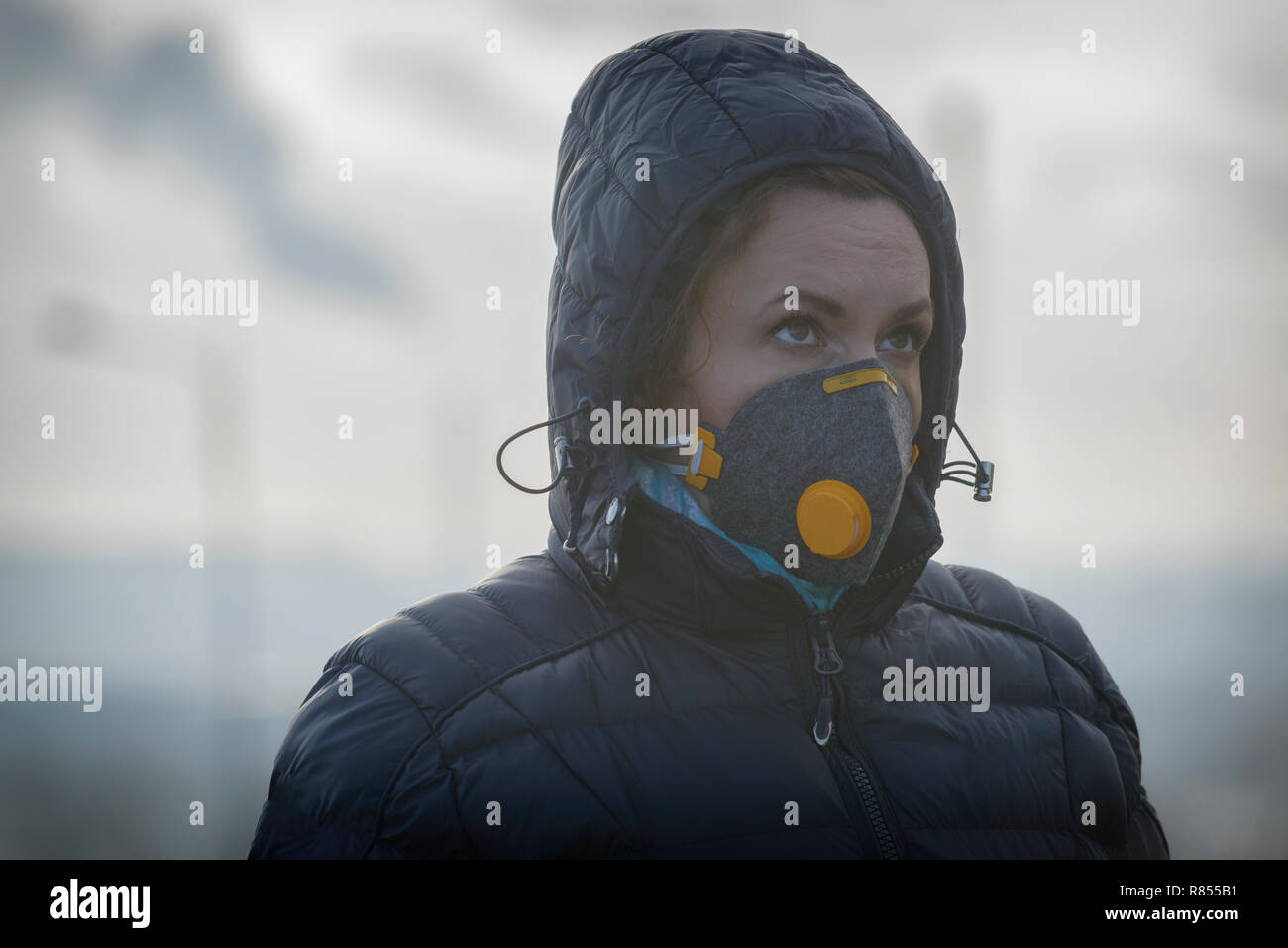 Woman wearing a real anti-pollution, anti-smog and viruses face mask; dense smog in air. - Stock Image