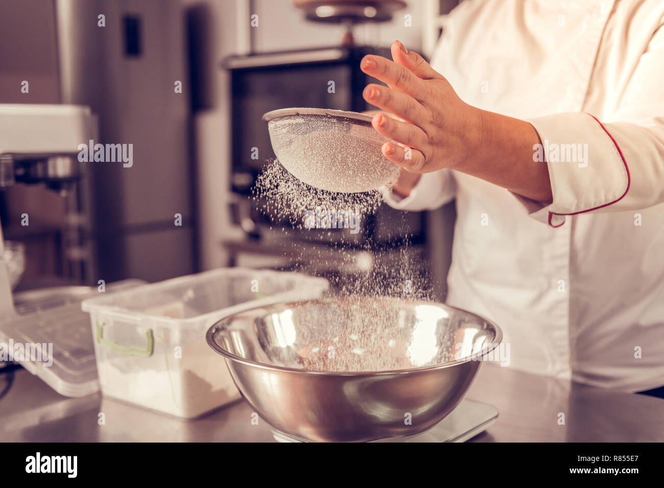 Kitchen equipment. Close up of a flout sifter being in female hands during the process of food preparation - Stock Image