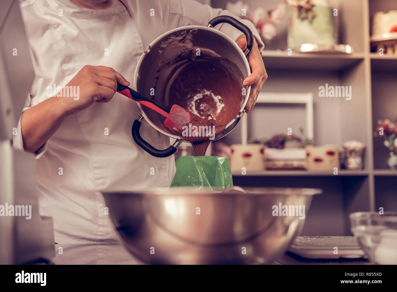 Cooking process. Nice professional cook putting the dough in the pastry bag while preparing the cake - Stock Image