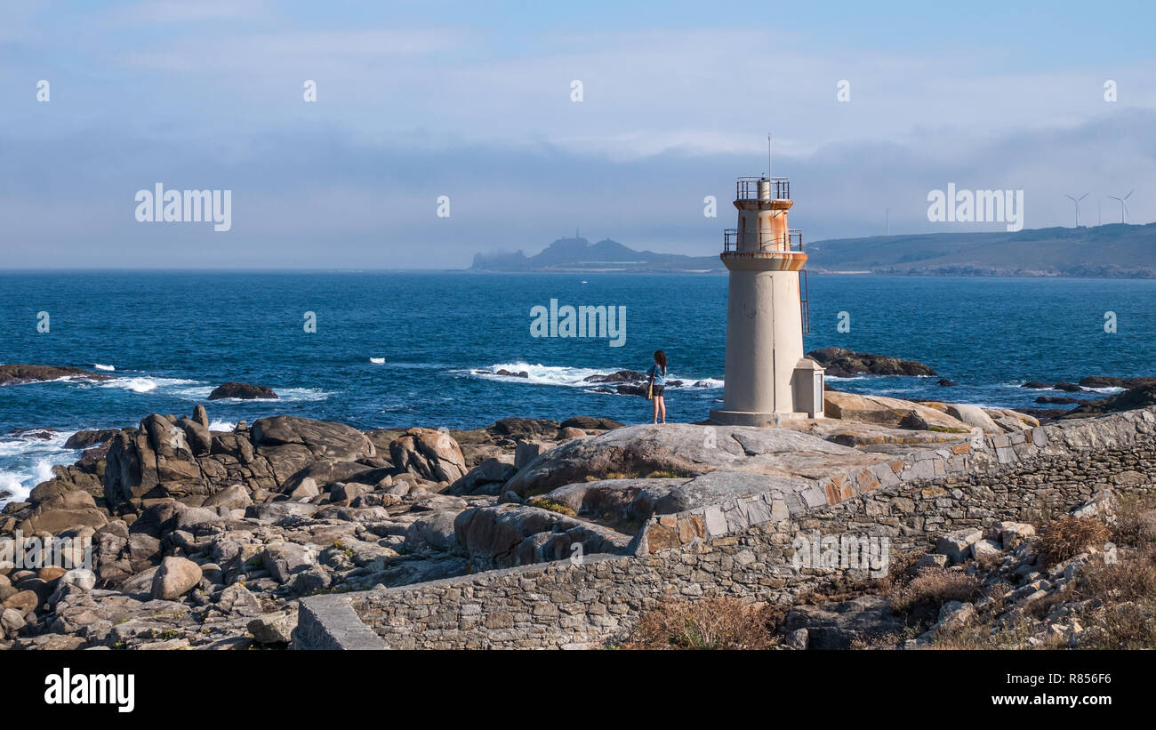Lonely girl looking over the sea at Punta da Barc lighthouse, next to the Sanctuary of Virxe da Barca in Muxia, Galicia, Spain - Stock Image