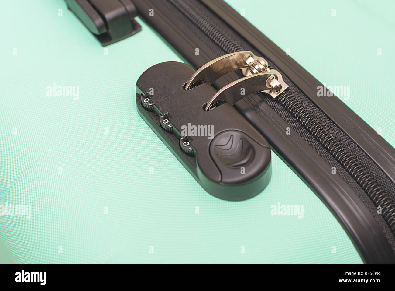 Closeup of a security padlock with three numbers on green suitcase Stock Photo
