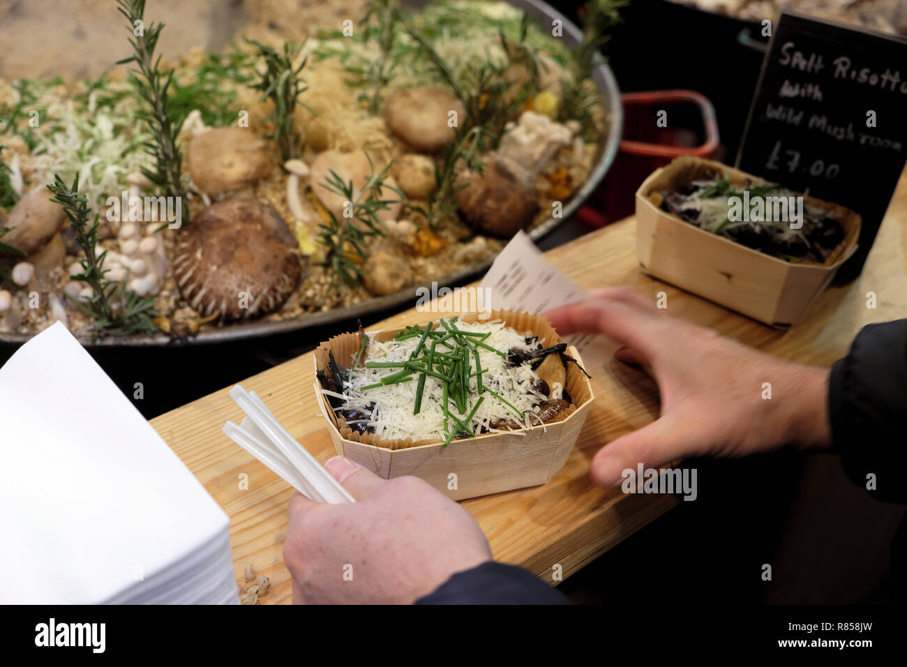 A person customer buying wild mushroom spelt risotto at a Borough Market Christmas food stall in Southwark, South London England UK  KATHY DEWITT Stock Photo