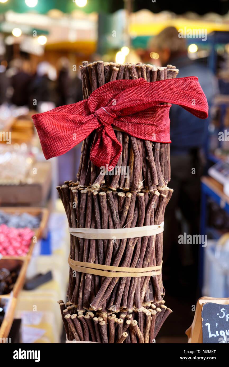 Liquorice raw sticks (licorice) Glycyrrhiza glabra with a red Christmas bow on a stall at Borough Market Christmas in London England UK   KATHY DEWITT - Stock Image
