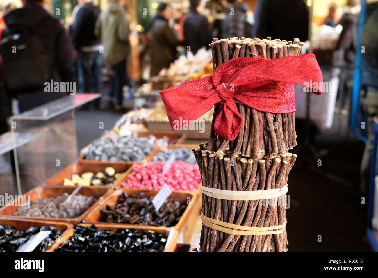Borough Market Christmas raw liquorice sticks (licorice) Glycyrrhiza glabra with a red Christmas bow on sweets stall London England UK   KATHY DEWITT - Stock Image