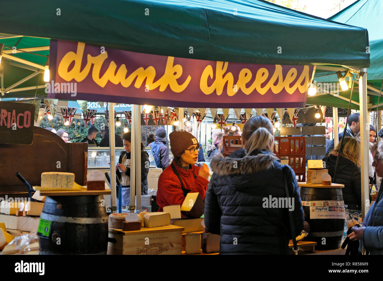 Young women serving a customer at the DRUNK CHEESES  Italian cheese stall at Borough Market Christmas food markets  in South London England UK Stock Photo