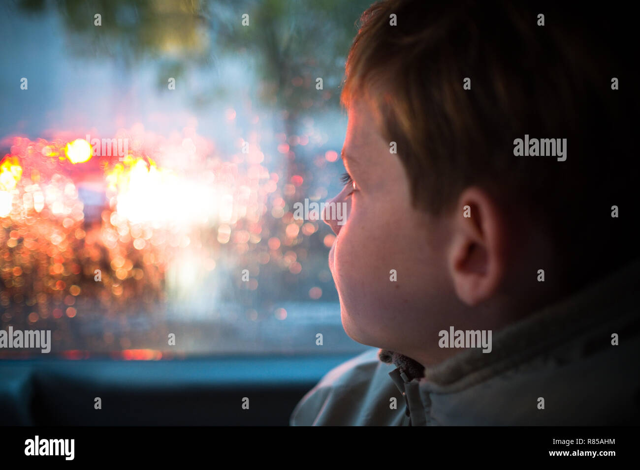 close up side profile of 11 year old boy inside car on way to school looking out of car window  at a passing car in the rain - Stock Image