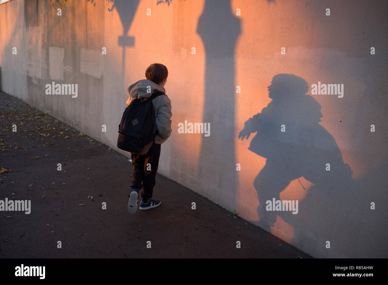 early morning shot of 11 year old boy with school bag playing with his shadows on wall on his way to college - Stock Image