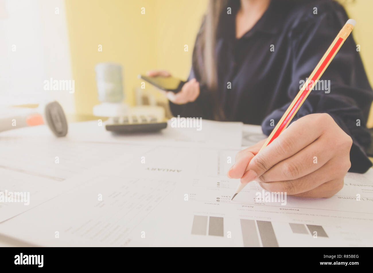 Business concept of financial and accounting with human hand are holding smartphone and writing, Finance report and with paper sheet of planning data  Stock Photo