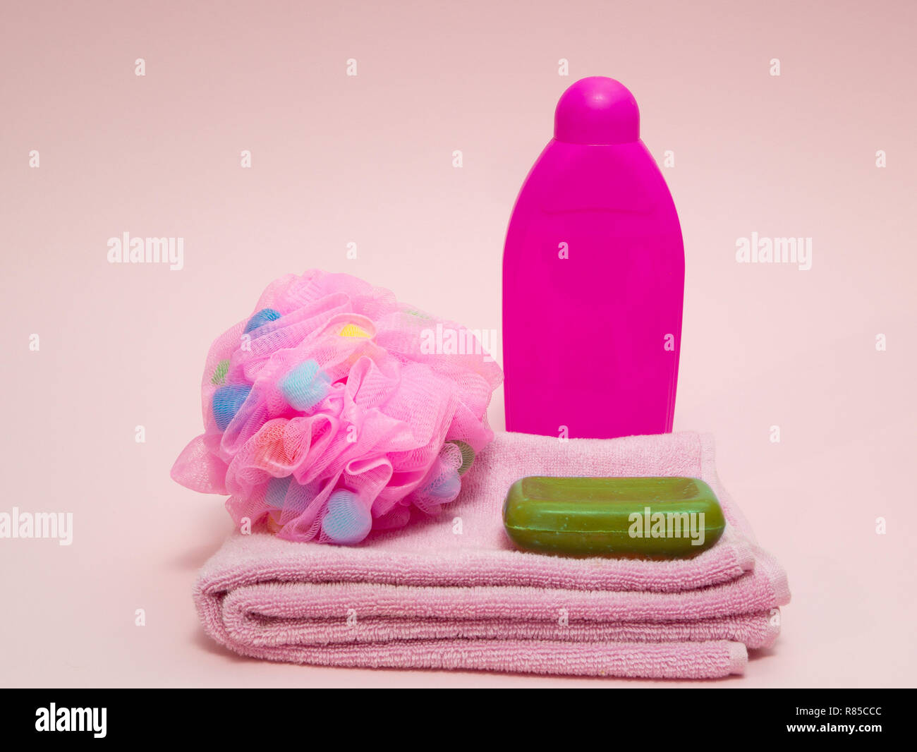 set of woman aroma therapy shower preparing equipment like towel, puffy sponge, green fruit aroma soap and shampoo on pink background - Stock Image