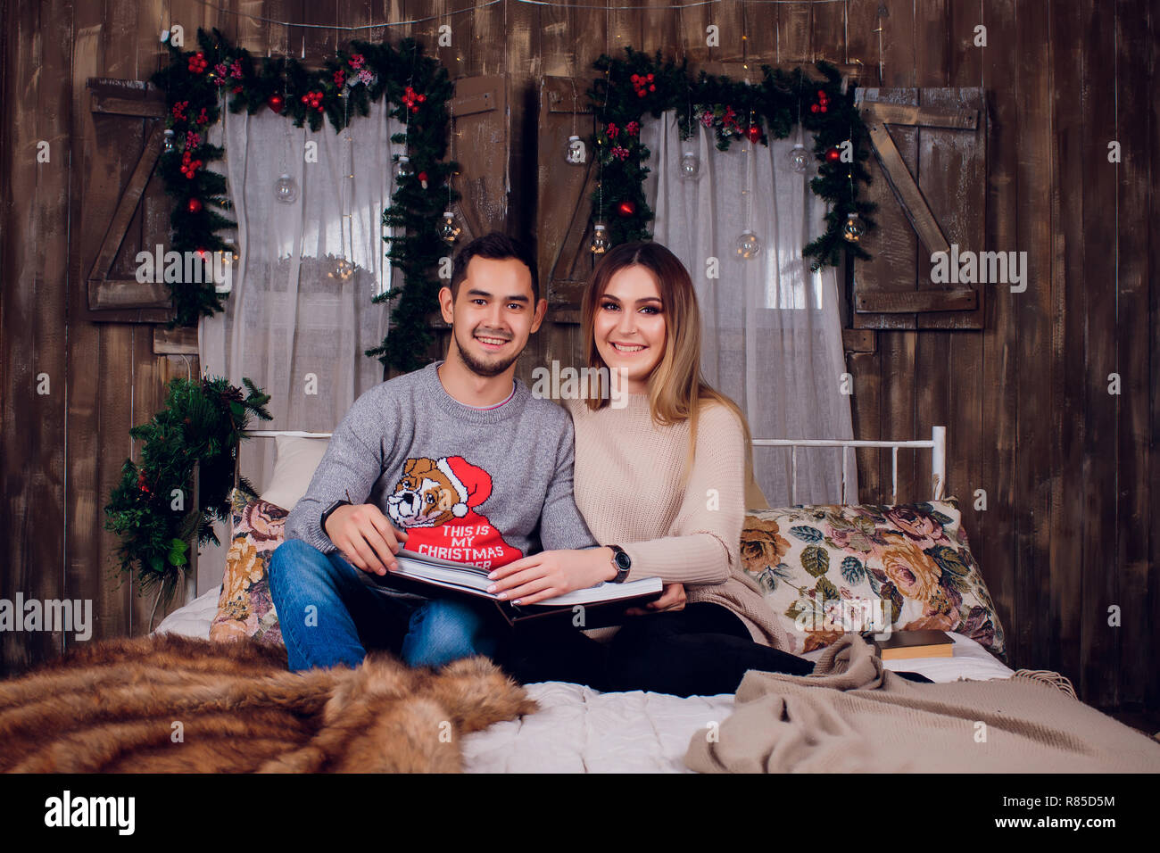 Spending nice time at home. Beautiful young loving couple bonding to each other and smiling while woman holding a book. - Stock Image