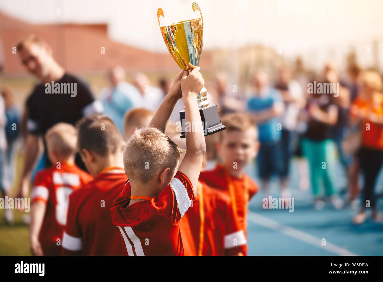Kids Winning Sports Competition. Children Soccer Team with Trophy. Boys Celebrating Football Championship in Primary School Fooutball Tournament - Stock Image