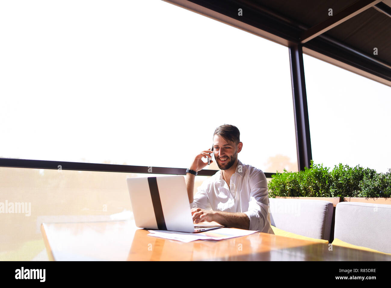 Responsible realtor browsing new information by laptop and calli - Stock Image