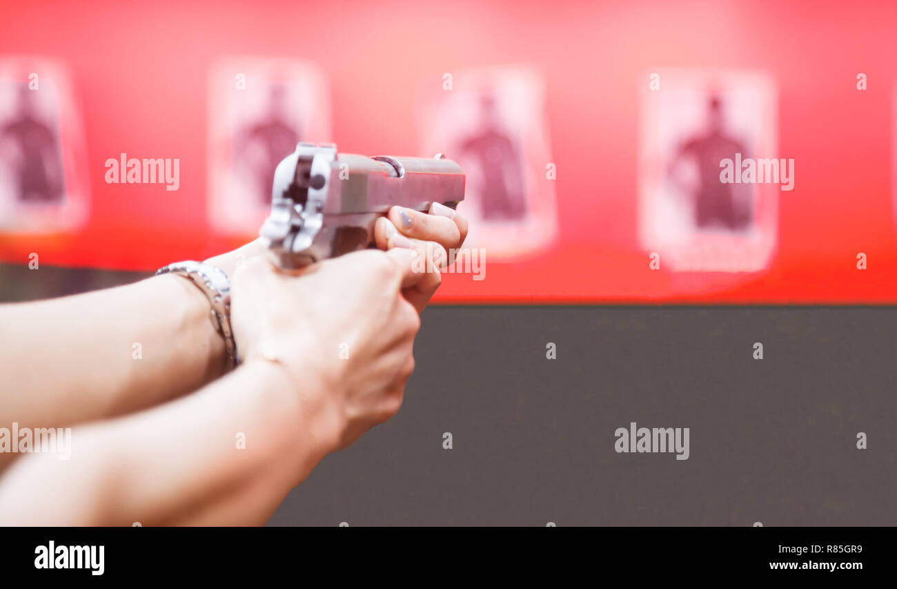 Woman Both Hands holding magnum gun, index finger on trigger, aiming ready to shoot on targets on red wall background. Sport, Recreation, Weapon, Fire - Stock Image