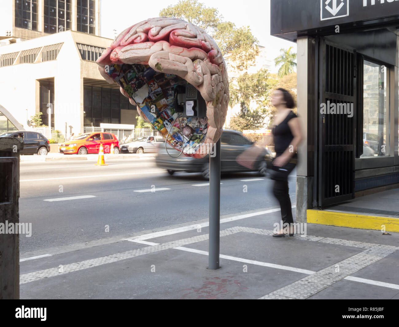 "Passerby walks past behind giant brain-shaped phone booth street art installation, as part of ""Call Parade"", Avenida Paulista, Sao Paulo, Brazil - Stock Image"