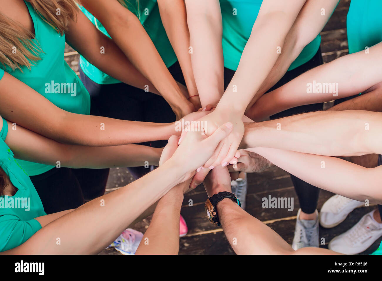 Portrait of happy fit young female friends stacking hands. Stock Photo