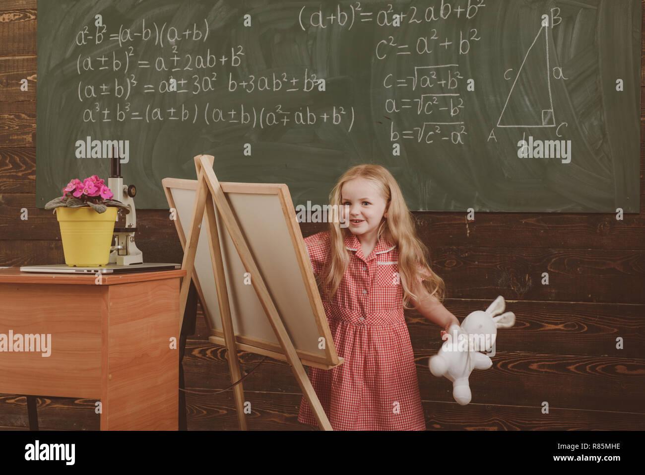 Girl draw picture in art school. Little artist paint on studio easel, art education, vintage filter - Stock Image