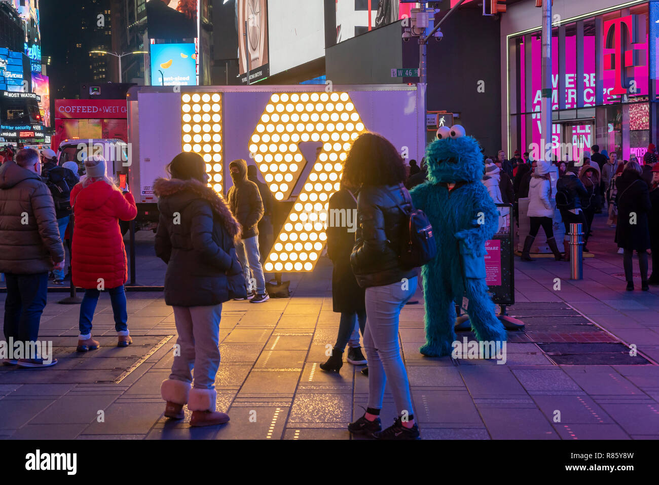 New York,NY/USA-December 12, 2018 Visitors to Times Square in New York pose in front of the two seven-foot-tall numerals '1' and '9' in Times Square in New York on Wednesday, December 12, 2019 .  The '19' will be part of the led display atop One Times Square which will light up at midnight January 1 spelling out '2019' ushering the New Year. The seven-foot tall numbers use energy efficient LED bulbs which will last the entire year, never having to be changed.  (© Richard B. Levine) Credit: Richard Levine/Alamy Live News - Stock Image