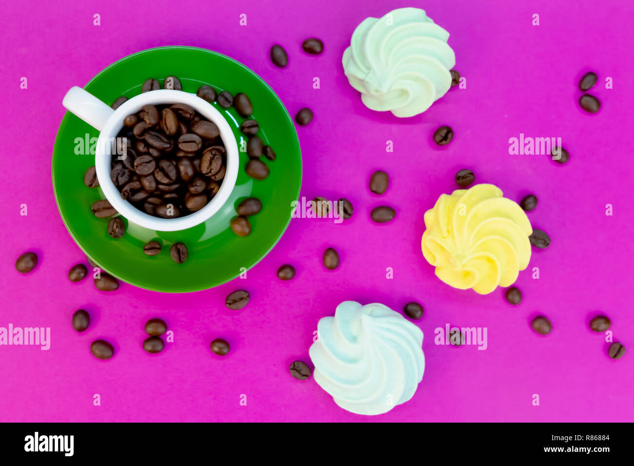 Coffee beans in cup on hot pink table with sweets, concept photograph with vivid colors Stock Photo