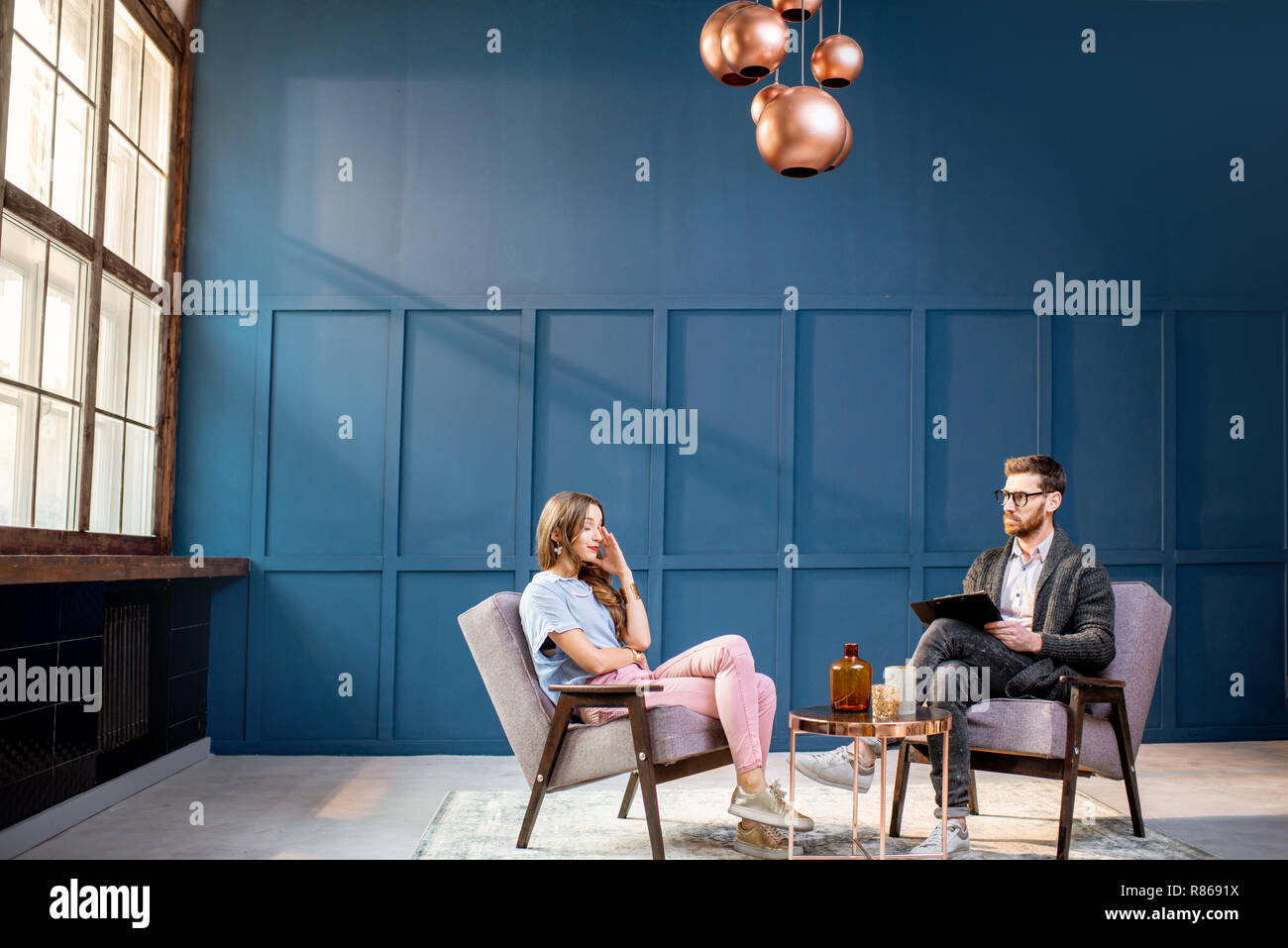 Woman Client Sitting With Male Psychologist On The Chairs