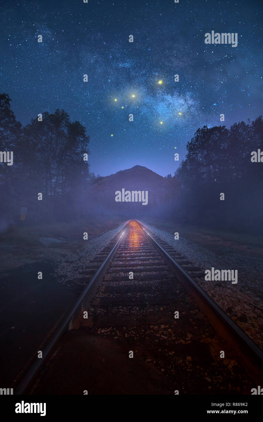 Mysterious lights in the sky over a rural landscape with train tracks leading off into the distance. Great for a book cover or science fiction themes. - Stock Image