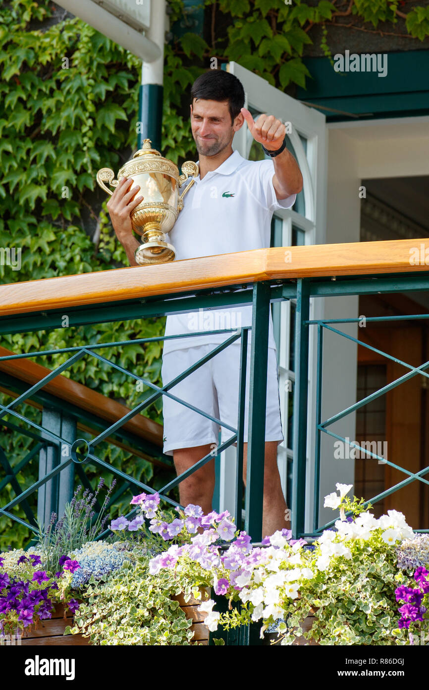 Novak Djokovic of Serbia celebrates with the trophy on Centre Court balcony during the Wimbledon Championships 2019 - Stock Image