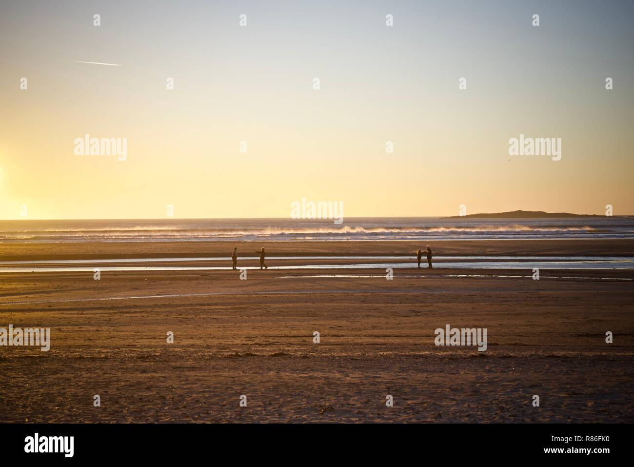 People walking on the beach in Rhosneigr, Anglesey, Wales, UK - Stock Image