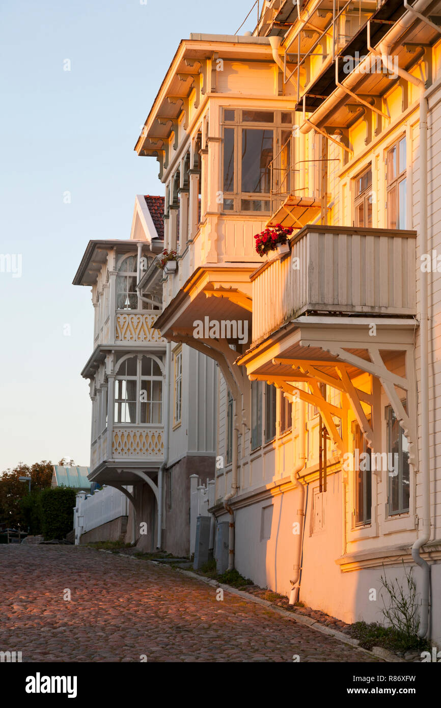 Typical old Swedish houses in the sunset in hilly paved street on the island of Marstrand, southwest Sweden in a summer evening. - Stock Image