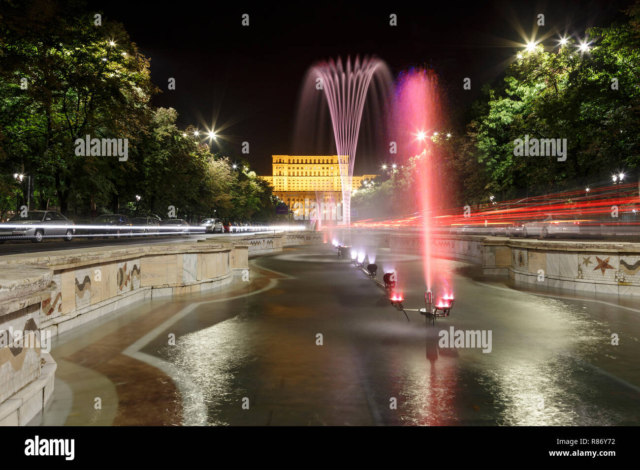 Building of Romanian parliament in Bucharest in a beautiful summer night, and fountains in front. Stock Photo