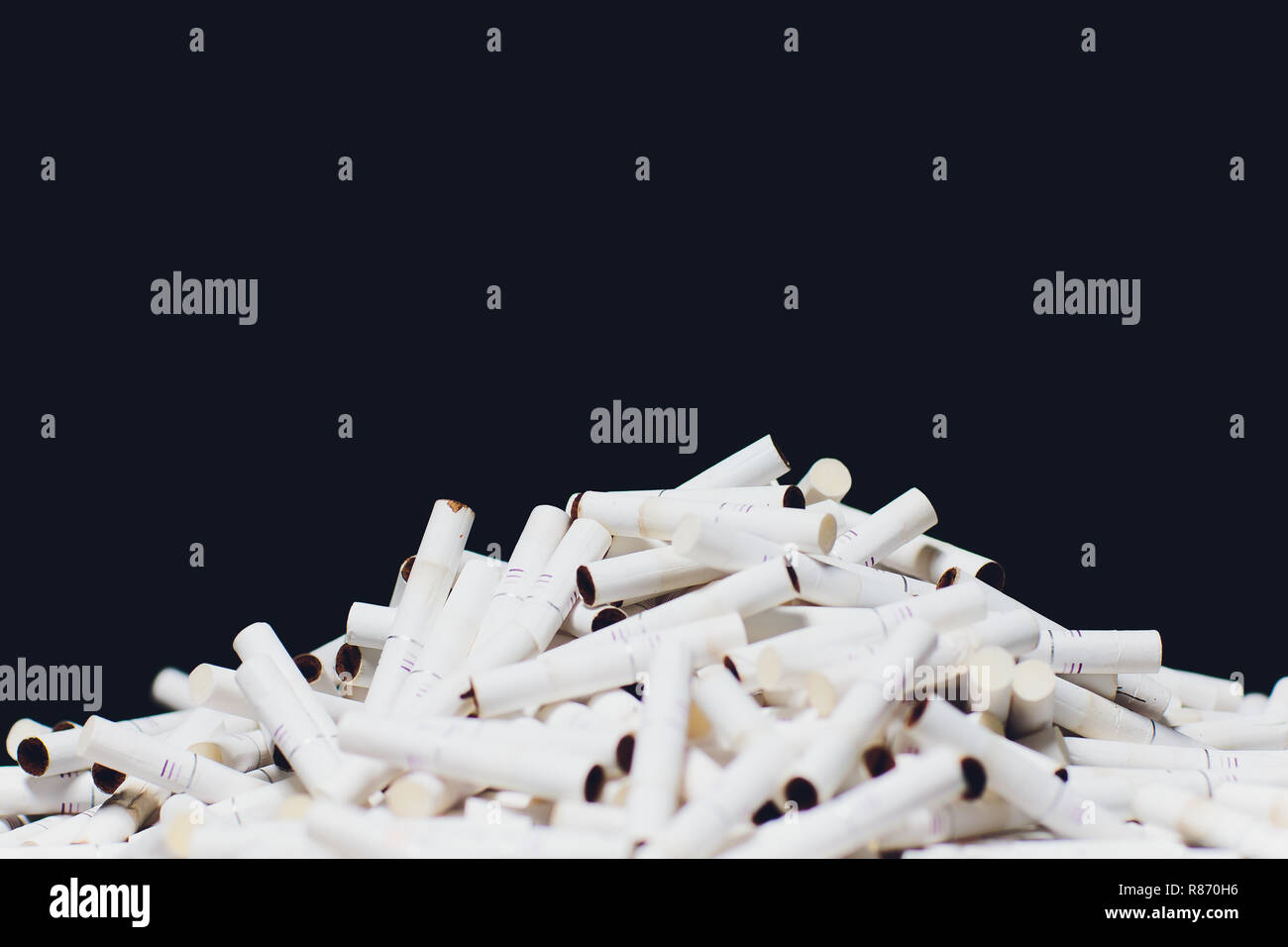 Newest electronic cigarettes, heating tobacco system IQOS, smoking, dark blue isolated on black background. mountain of used cigarettes, sticks - Stock Image
