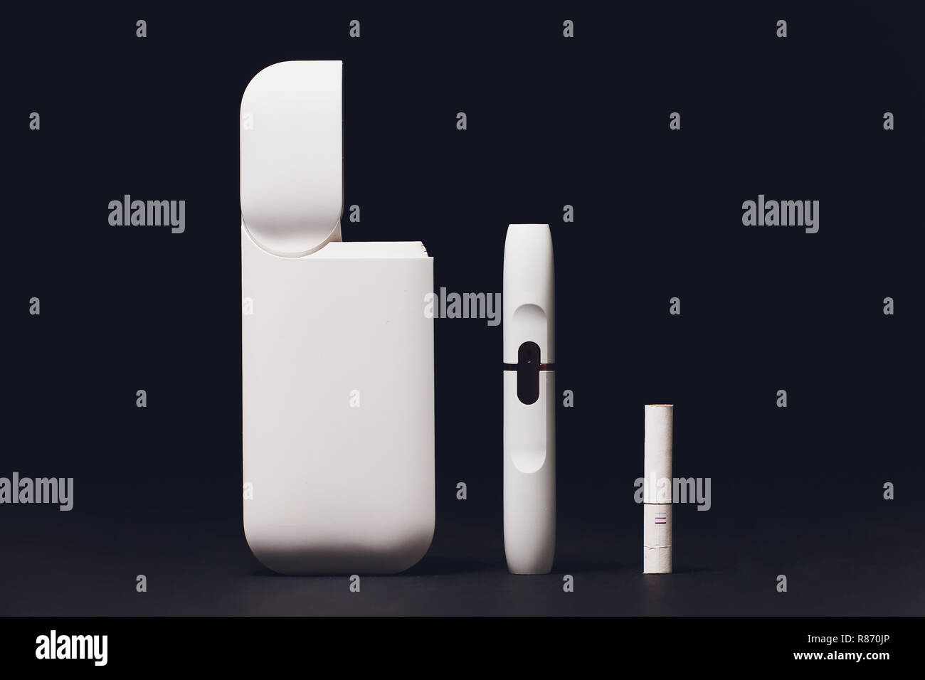 Newest electronic cigarettes, heating tobacco system IQOS, smoking, dark blue isolated on black background. white gadget Stock Photo