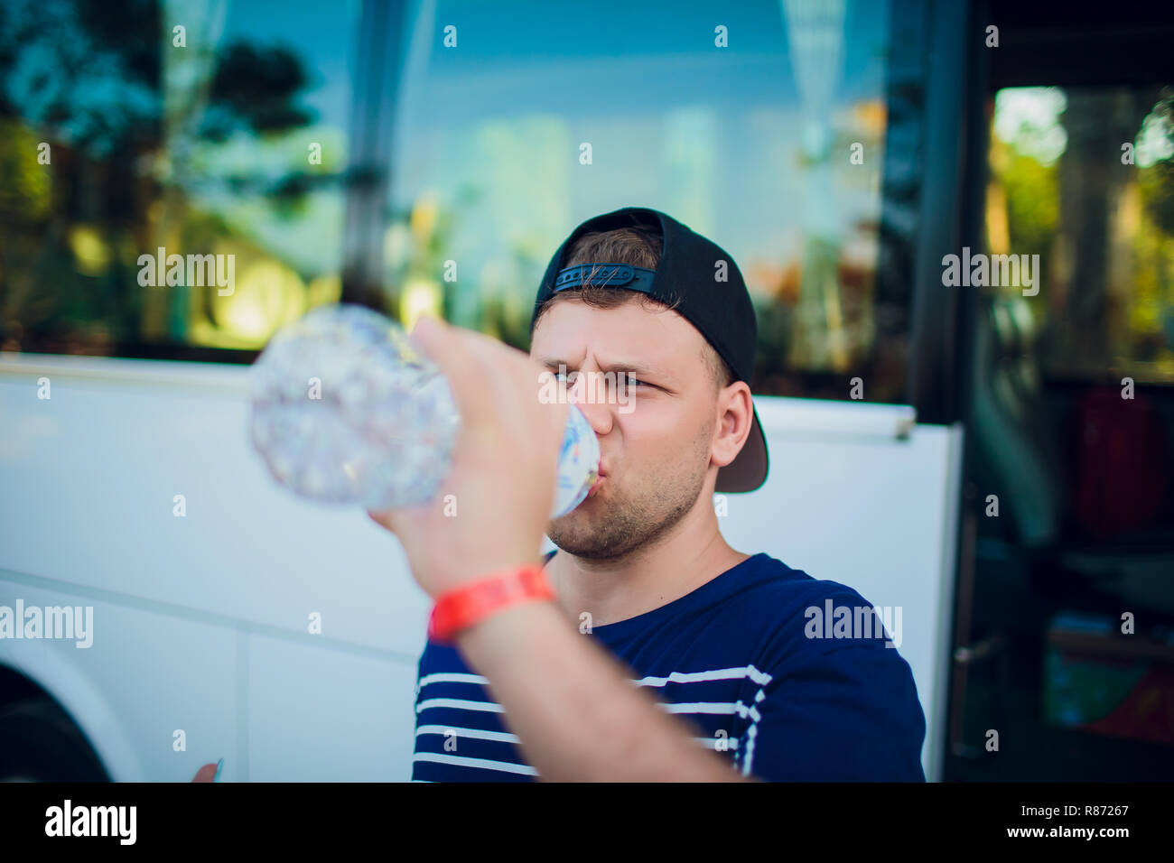 Handsome man drinking water after running outdoors on the background of the bus, tourist. Stock Photo