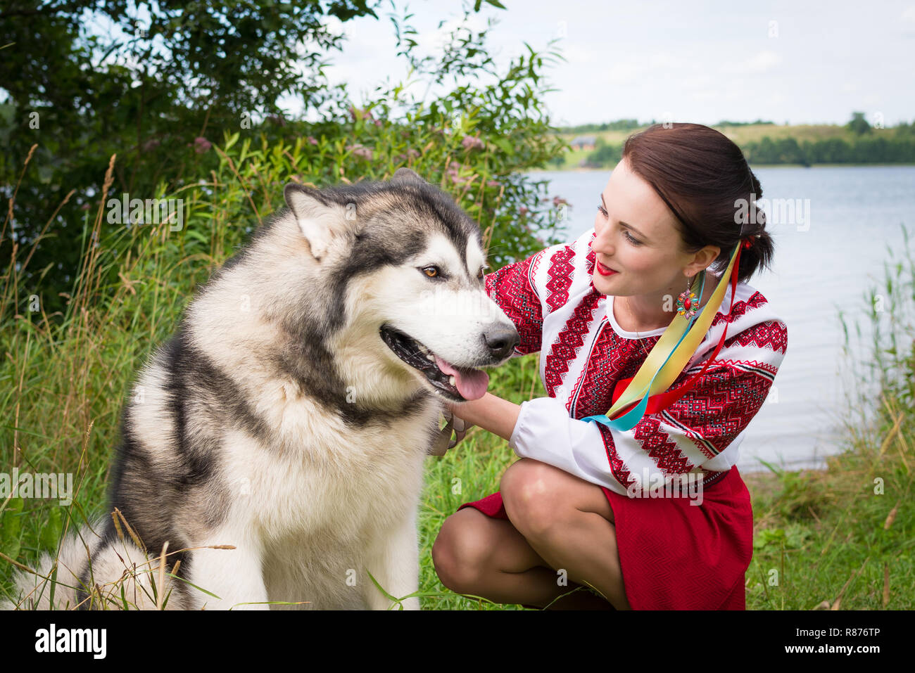 Girl dresses in a traditional Slavic attire petting a dog - Stock Image