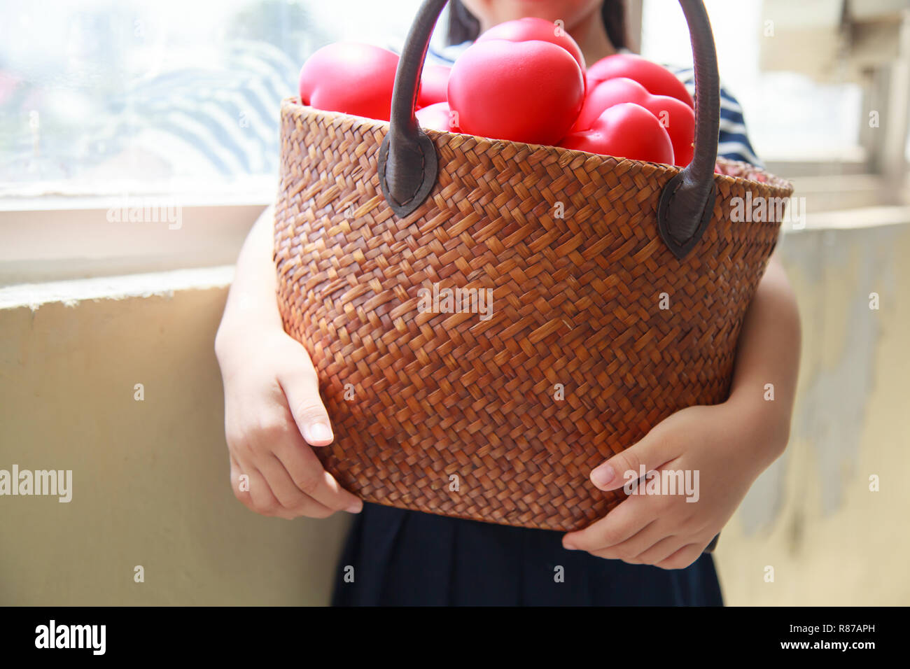 girl in navy blue striped dress handing basket of red hearts represents helping hands, family support, morale, purity, innocence, cheer up, loves, hos Stock Photo