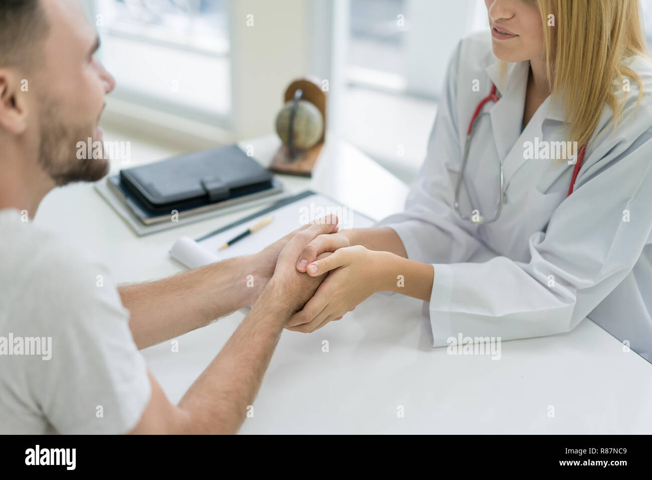 Doctor or psychiatrist consulting and diagnostic examining stressful man patient in medical clinic or hospital healthcare service center. - Stock Image