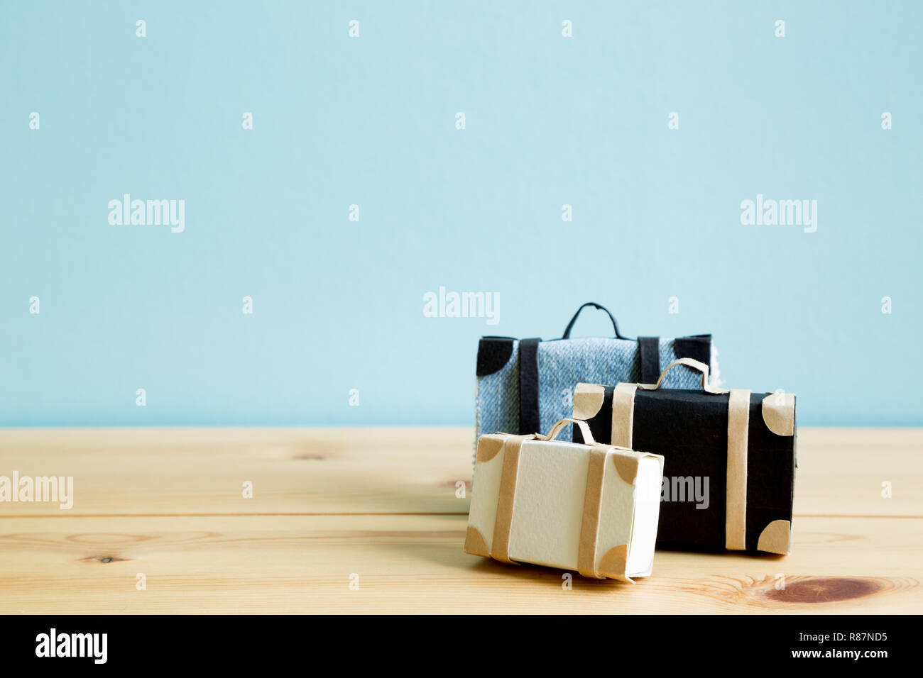 Travel suitcase on wooden table with sky blue background - Stock Image