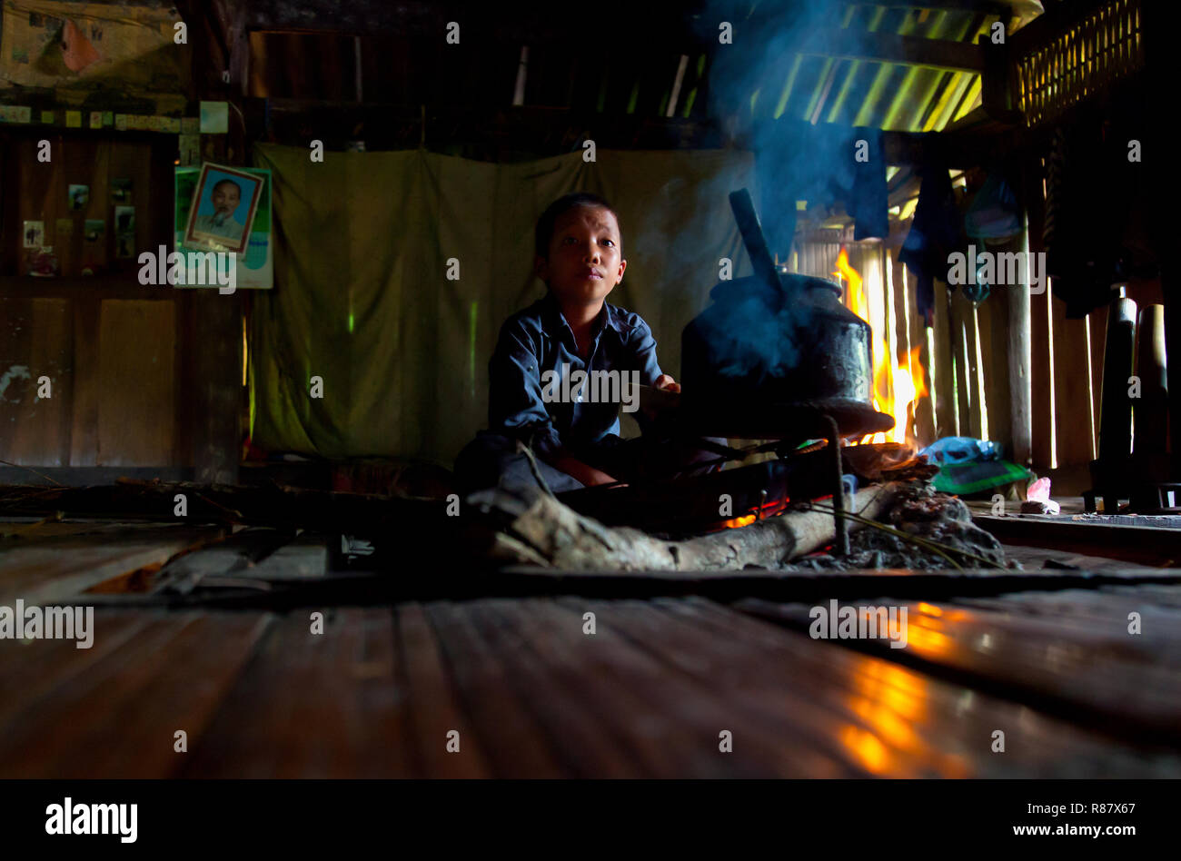 In the home of a family of minority people in Hoang Su Phi. A young boy attending the fire. Ha Giang province, in the mountainous northwestern part of - Stock Image