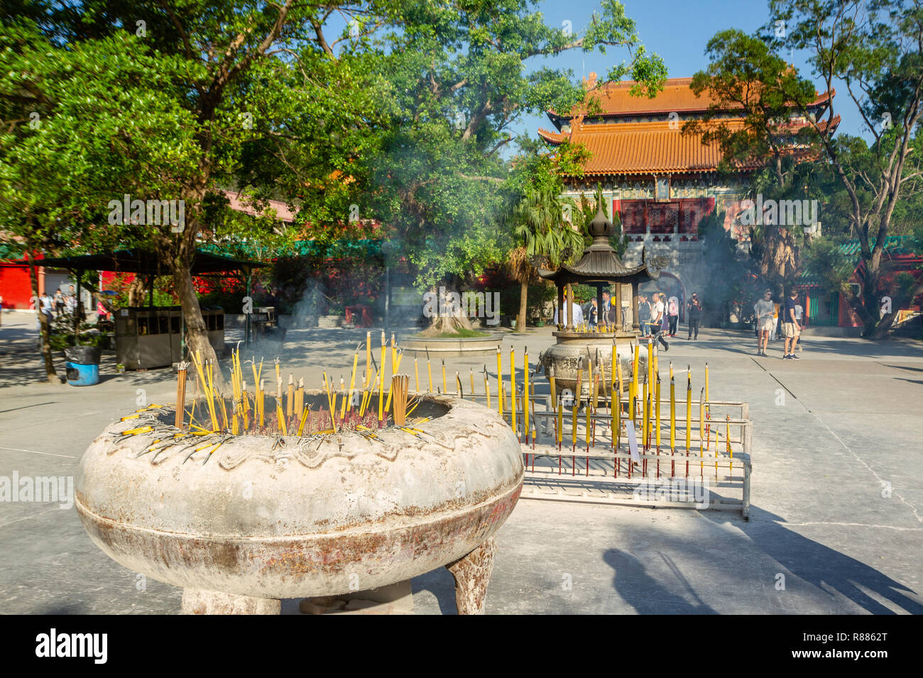 Yellow burning sticks of incense in large incense burner in front of buddhist temple at Po Lin Monastery, Lantau Island, Hong Kong, China. - Stock Image