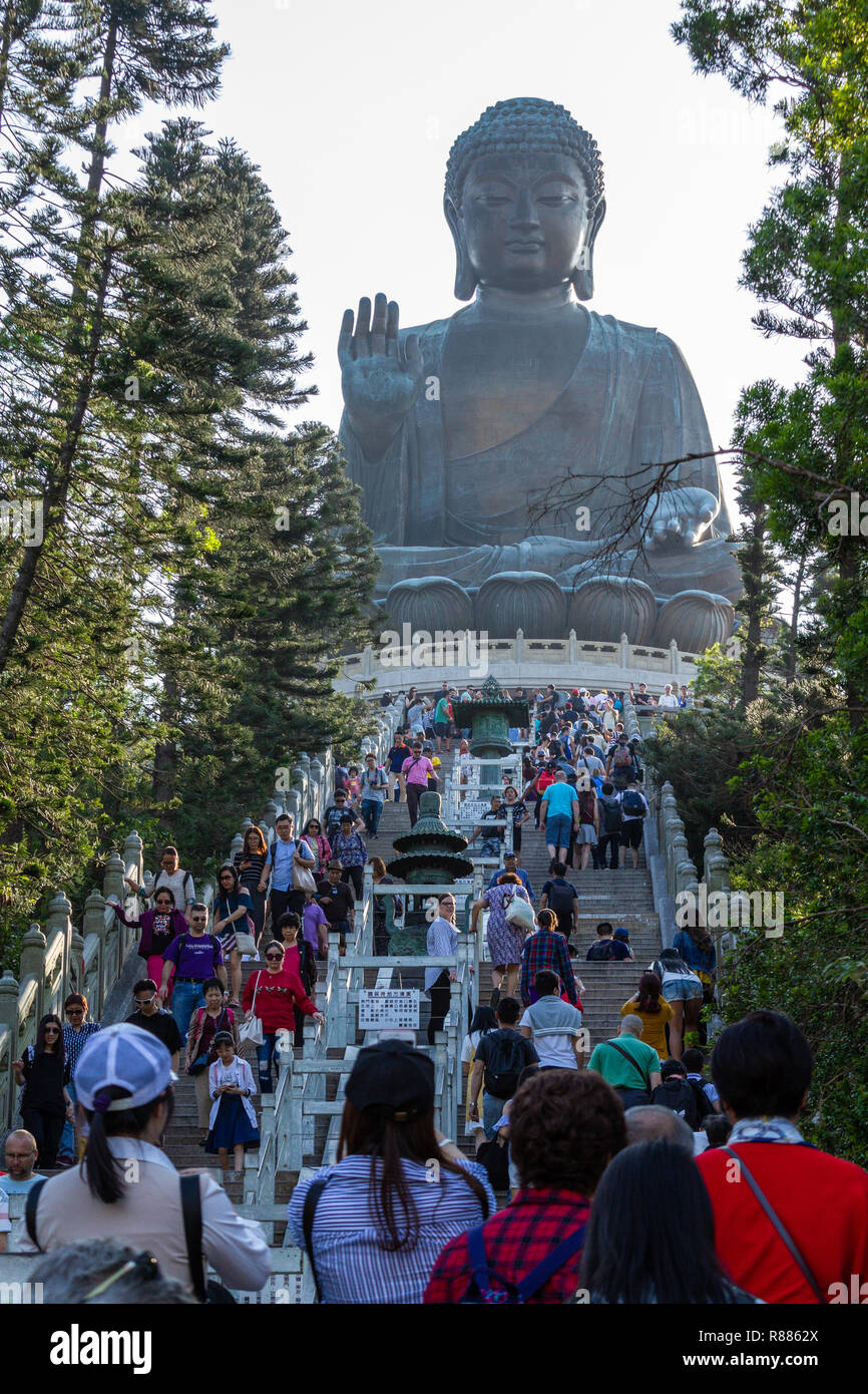 Vertical photo of people climbing stairs to the seated, bronze, Tian Tan Buddha at Po Lin Monastery on Lantau Island, Honk Kong, China. - Stock Image