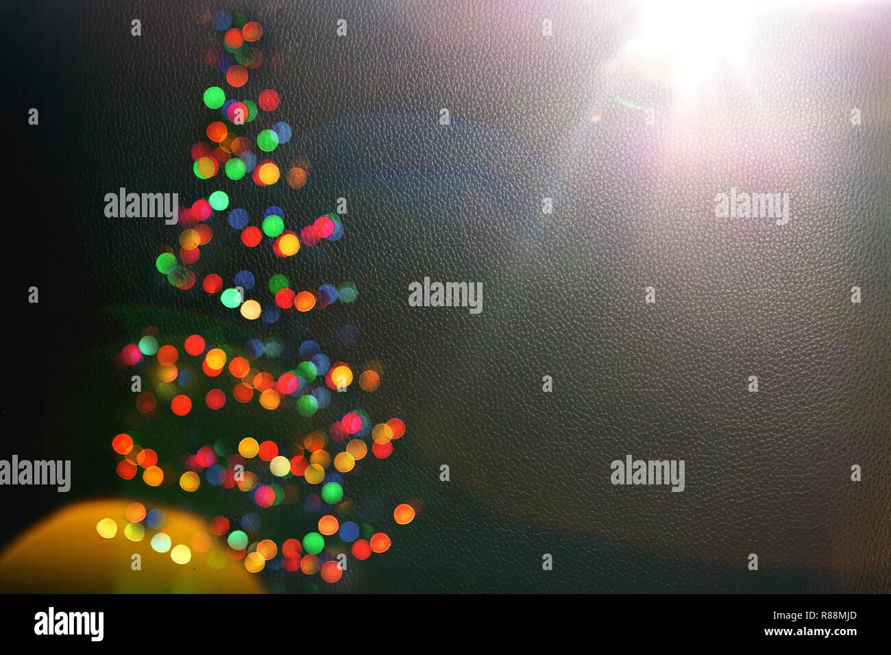 Bokeh silhouette of Christmas tree.blur light celebration on christmas tree on dark wall background. Abstract Christmas tree lights.Winter holidays greeting card.fairy lights.Copy space - Stock Image