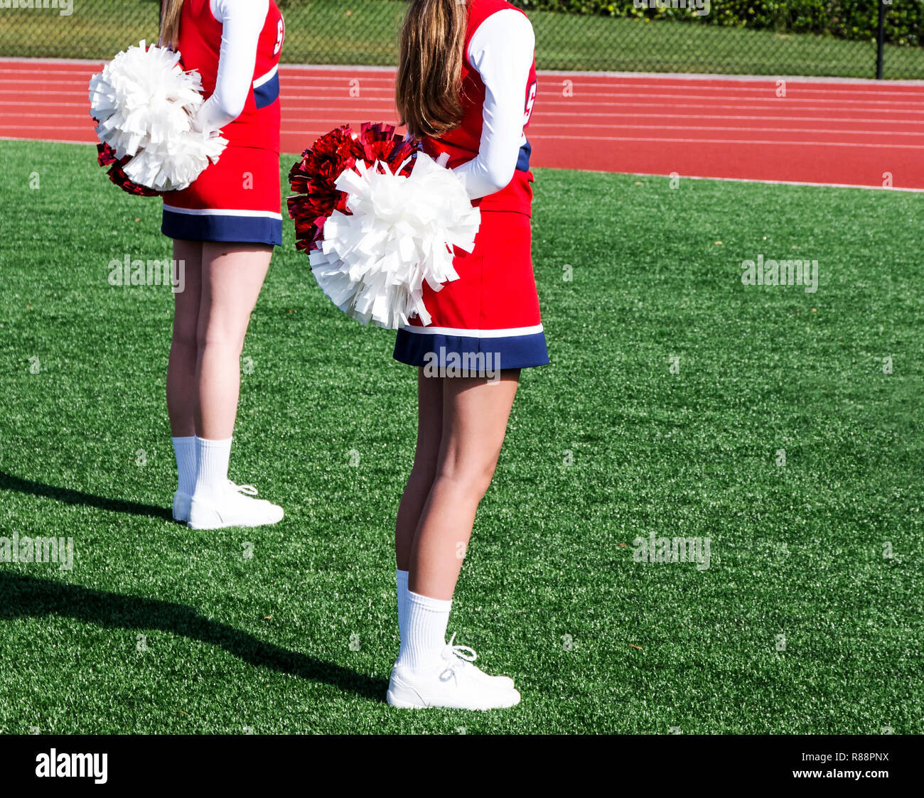 Two high school cheerleaders are standing at attention with their pompoms behind them getting ready to start their routine. - Stock Image