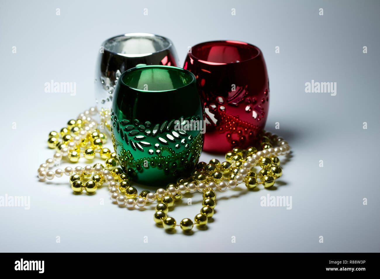 Abstract holiday decoration background with a trio of colorful modern metallic candle holders surrounded by reflecting metal beads - Stock Image