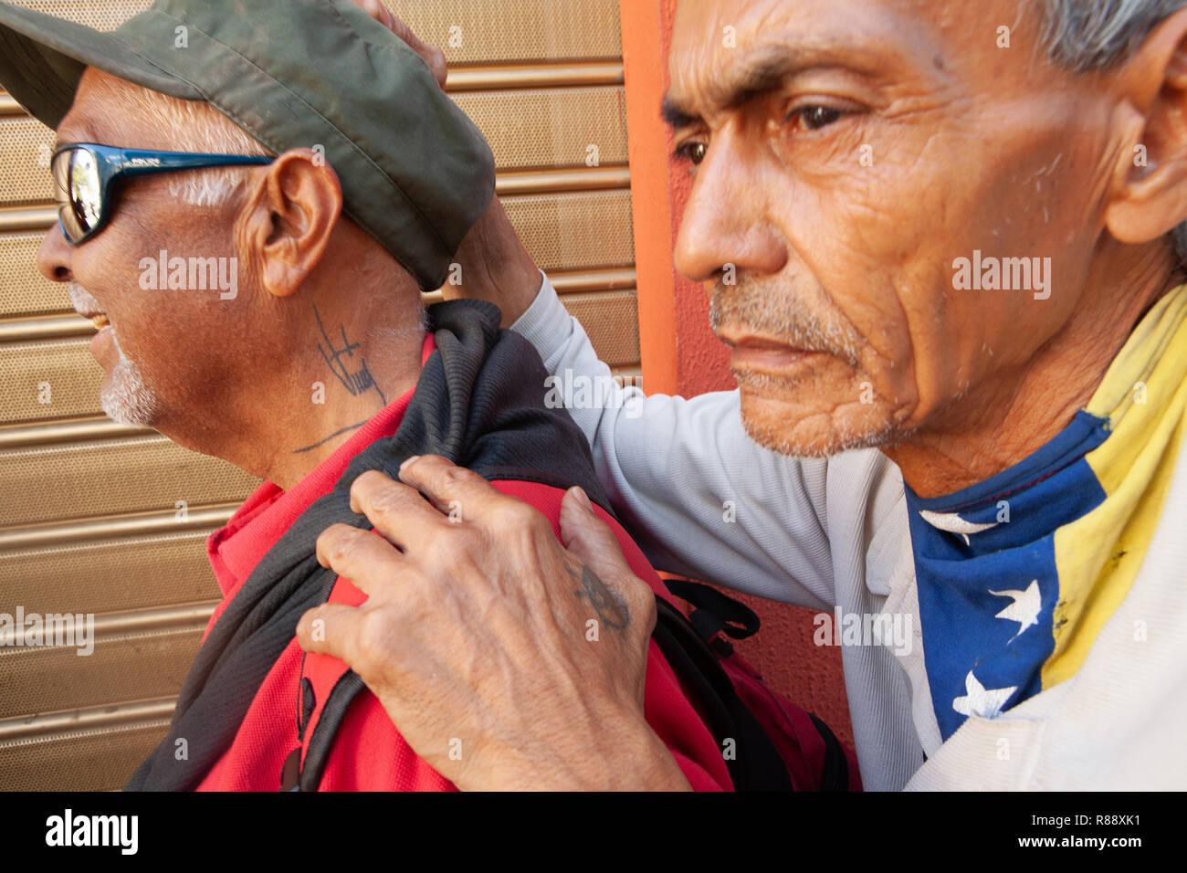 Two men with tattooed neck and hand wearing Venezuelan flag neckerchief, close up, Caracas, Venezuela, South America - Stock Image