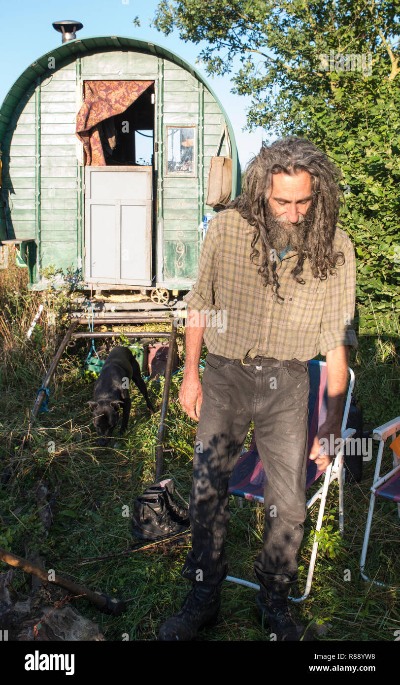 Peter the traveller with long untidy hair and beard in front of his wooden horse-drawn caravan on a roadside verge. - Stock Image