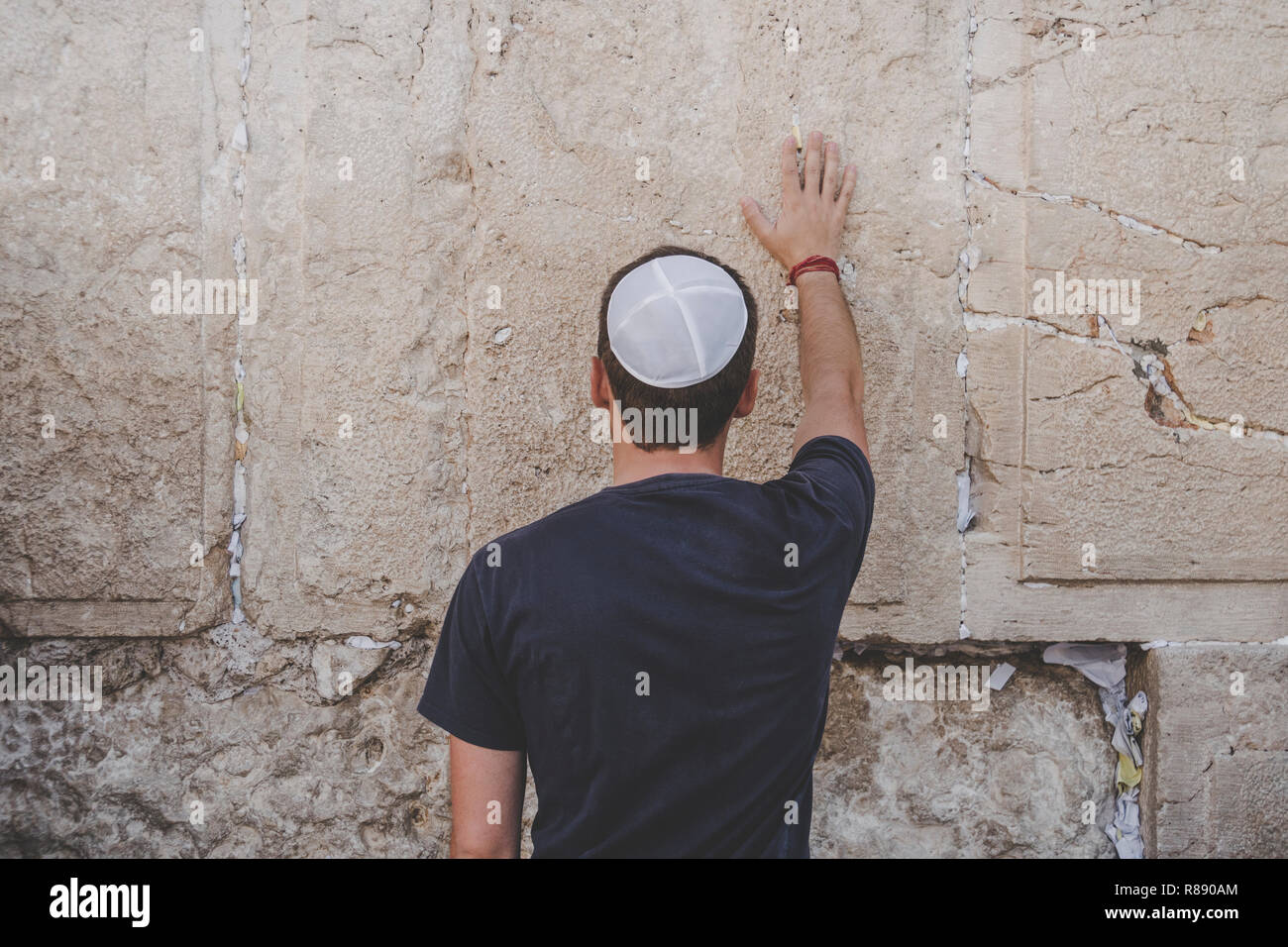 Man hand and pray paper on the Western Wall, Wailing Wall the Place of Weeping is an ancient limestone wall in the Old City of Jerusalem. Second Jewis - Stock Image