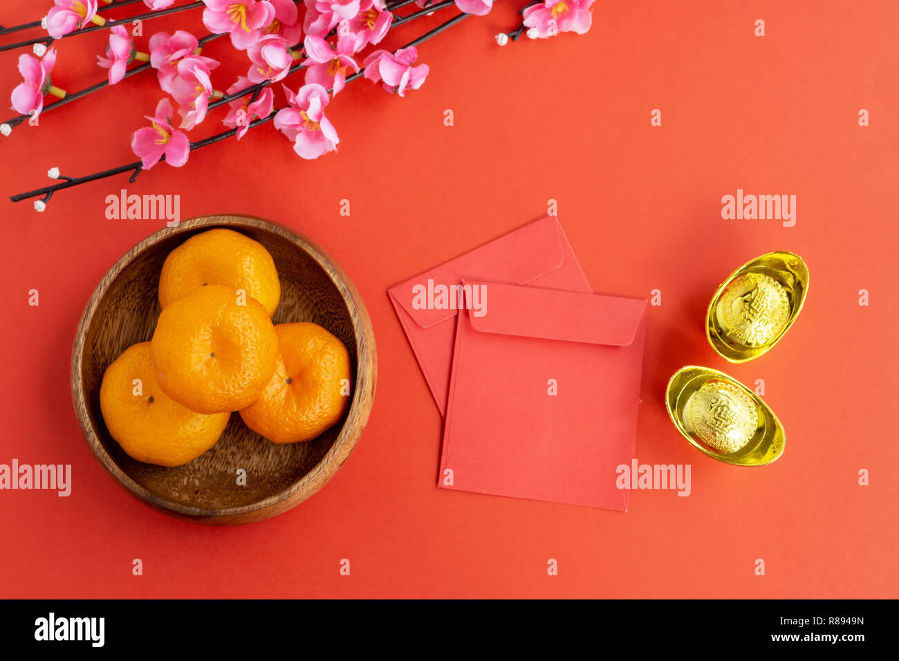 Flat lay Chinese New Year Background - Cherry Blossom, Mandarin Orange, Red Envelop and Golden Ingots on red background. Stock Photo
