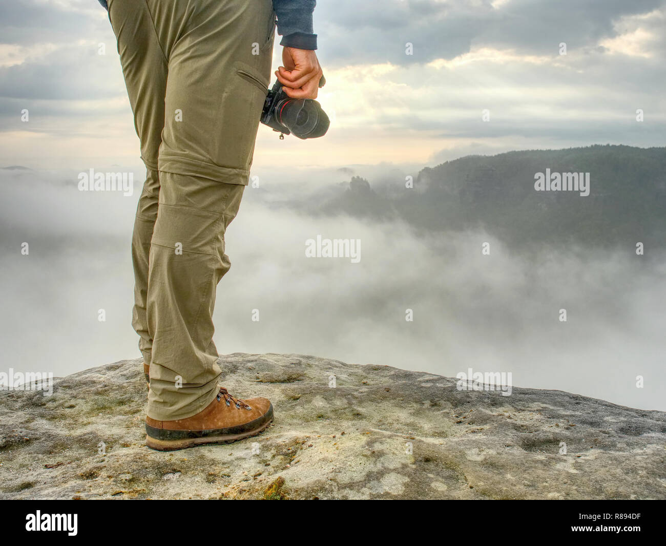 Landscape photograper with camera ready in hand. Man climbed up on exposed rock for fall photos with his digital camera. Cliff above misty autumn land - Stock Image