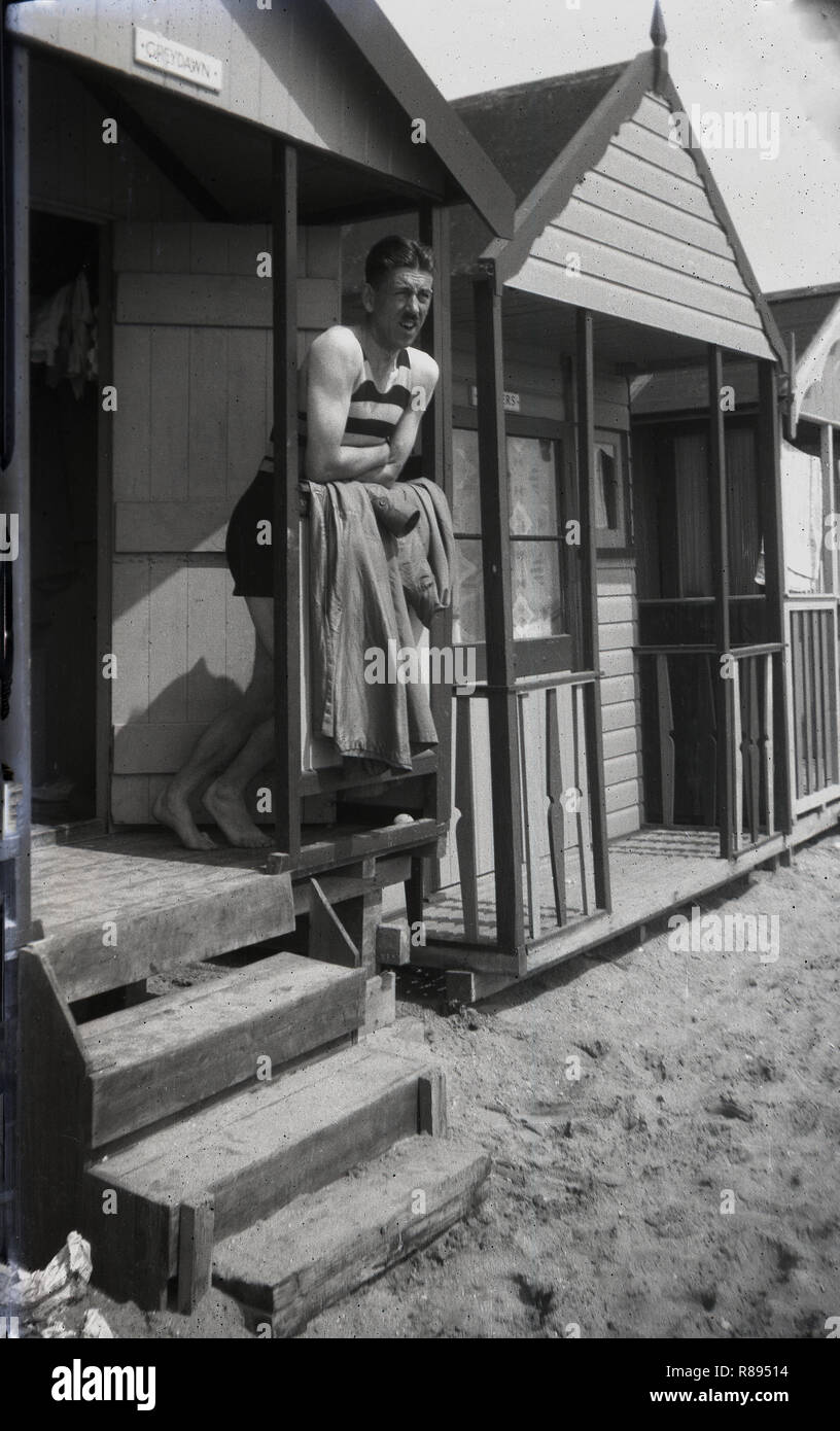 1930s, British man in  a stripy one-piece sleeveless swimsuit of the era, standing on a veranda of a beach hut at Southend-on-sea, England, U,a popular holiday resort for people living in Essex and London at this time. - Stock Image