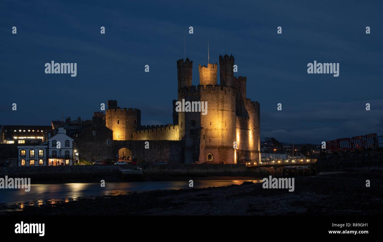 Caernarfon Castle, often anglicized as Carnarvon Castle, is a medieval fortress in Caernarfon, Gwynedd, north-west Wales. Taken here lit up at night Stock Photo