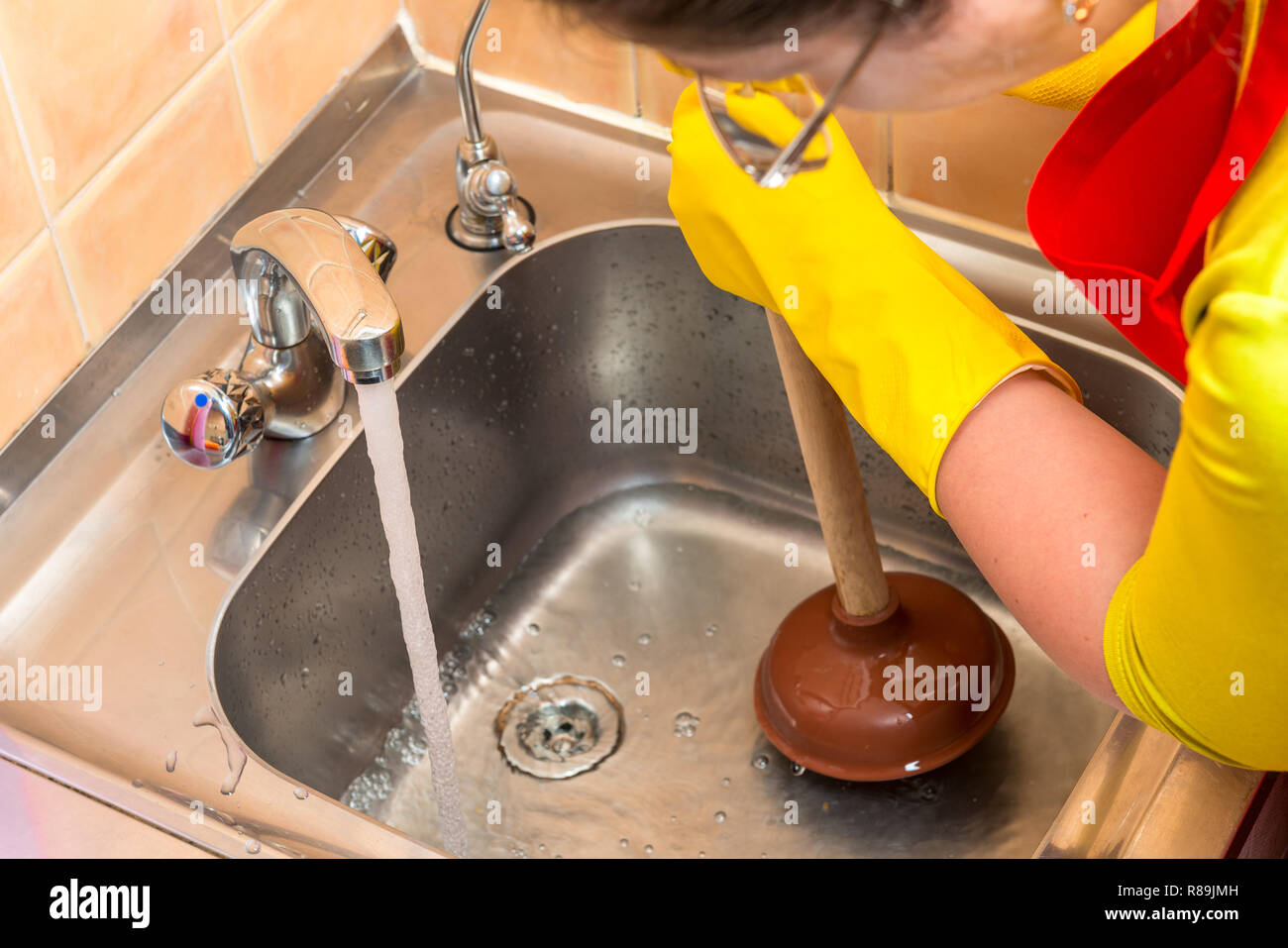Cleaning Clogged Pipes In The Kitchen Sink With A Plunger
