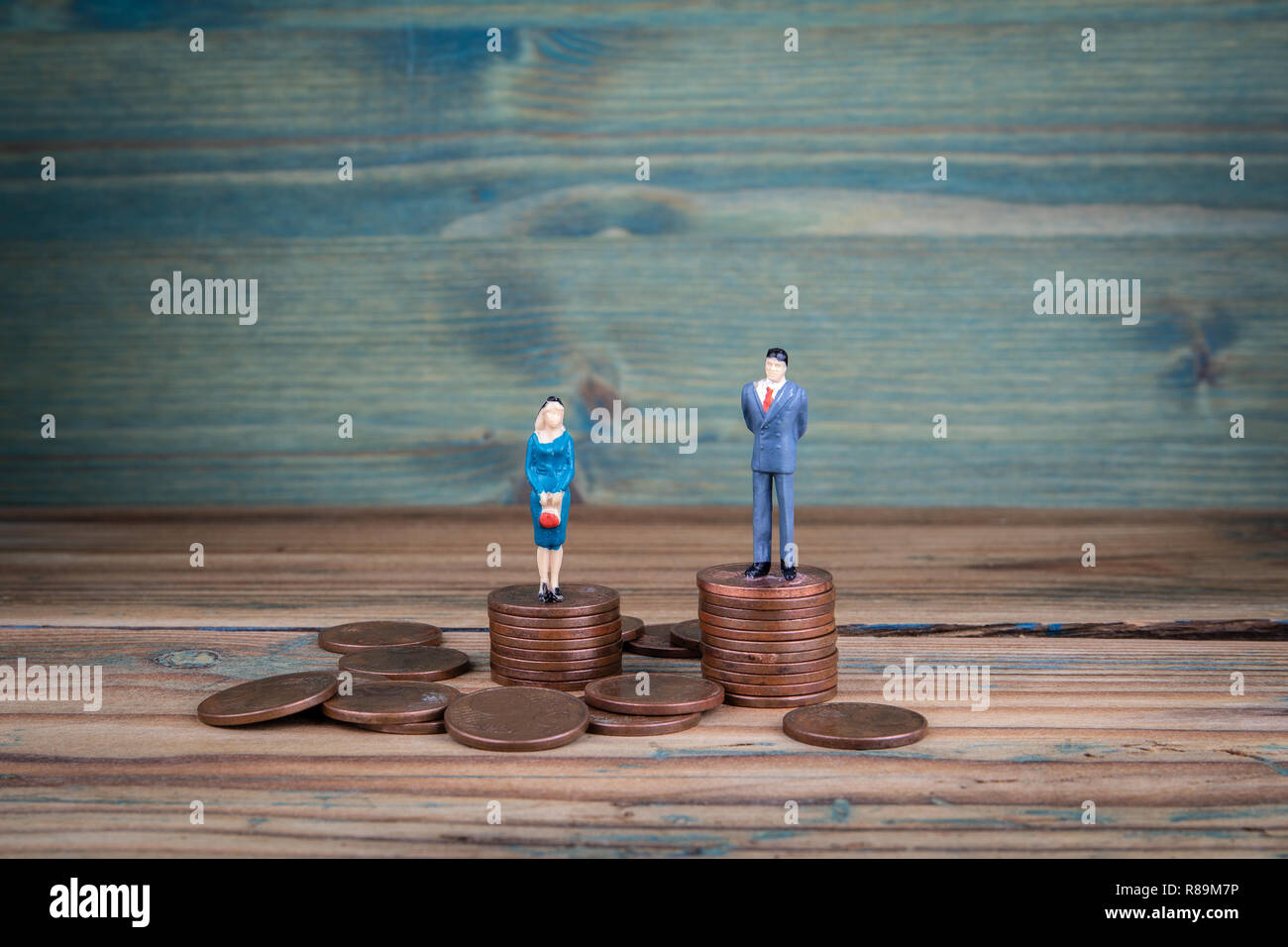Miniature people standing on piles of coins Stock Photo